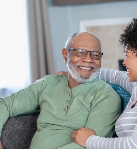 Adult daughter visits senior father in assisted living home